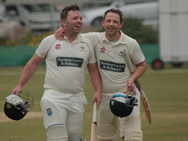 Sidmouth century maker Matt Cooke (left) makes his way off the field with skipper Nick Gingell after reaching his ton with a single off the final ball of his side