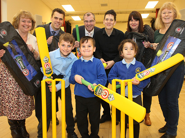 Nick Henderson and Rachel Anderson-Stacey (in the middle of the back row) handing over Kwik Cricket bags to primary school head teachers