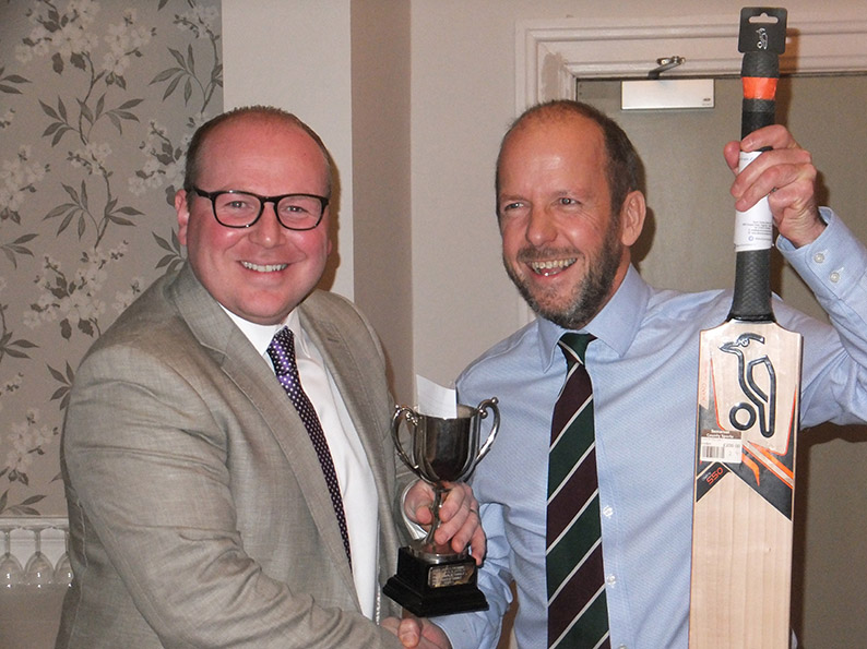 Bobby Marshall of Sidmouth CC sponsors Harrison Lavers & Potburys presents the raffle-prize bat to Charlie Dibble