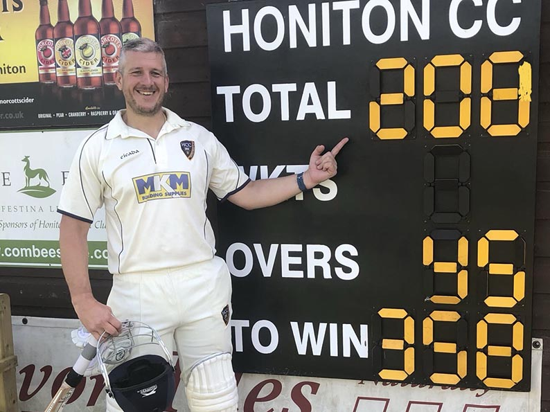 Dave Haysom poses by the scoreboard after his history making innings