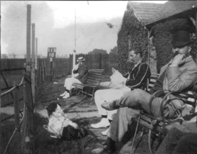 A photo dated 1894 of H B Mapleton sitting in the pavilion enclosure at South Devon during a game