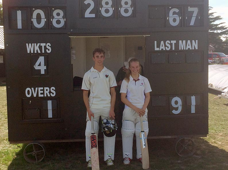 Sam and Emma Corney in front of the Topsham scorebox showing their scores in the record stand of 197