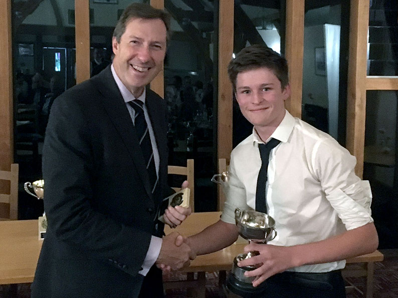 Best young cricketer Morgan Hargreaves accepting his trophy from Chris Hart