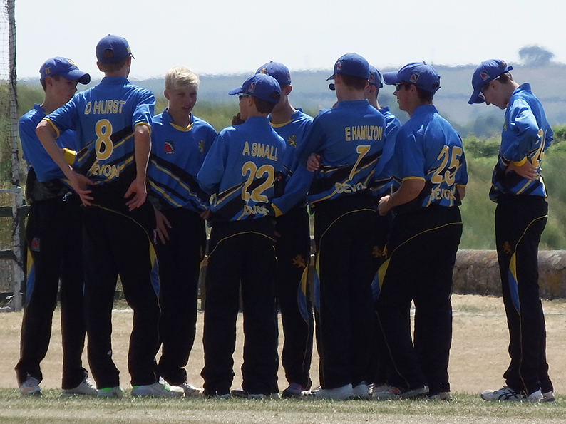 Devon U15s in a huddle after taking a wicket